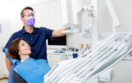 Male Dentist Explaining Xray To Female Patient In Clinic